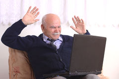 Grandfather and computer. The old generation and new technologies in the future of the game Royalty Free Stock Images