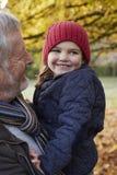 Grandfather Cuddling Granddaughter On Autumn Walk Stock Photography