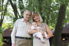 Grandfather with daughter and granddaughter standing in a garden Stock Photo