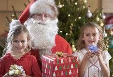 A grandfather dressed as Santa Claus with his grandchildren Royalty Free Stock Image