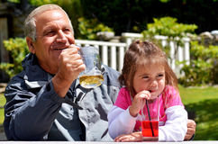 Grandfather drinks with his grandchild royalty free stock photography