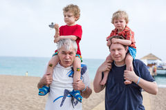 Grandfather and father giving two boys ride on shoulders. On the beach in summer Stock Photography
