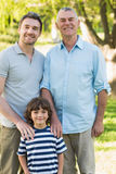 Grandfather father and son smiling at park Stock Photos