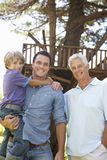 Grandfather, Father And Son Standing By Tree House Together Royalty Free Stock Images