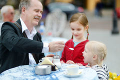 Grandfather feeding frothy milk to his grandchild Royalty Free Stock Image