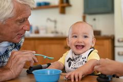 Grandfather feeding happy little boy royalty free stock photography