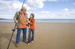 Grandfather with fishing rod smiling at granddaughter (9-11) on beach Stock Photos