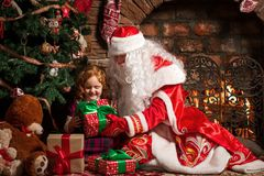Grandfather Frost gives a gift a little girl. Grandfather Frost gives a gift a little girl sitting in a chair. Fireplace and Christmas tree in the background Royalty Free Stock Image