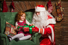 Grandfather Frost gives a gift a little girl sitting in a chair Stock Images