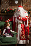 Grandfather Frost looks at the little girl sitting in a chair. Fireplace and Christmas tree in the background Royalty Free Stock Photography