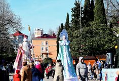 Grandfather frost and snow maiden are on the area of the city of Tuapse to the tree and rise above the audience. royalty free stock photo
