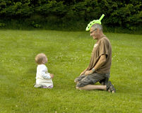 Grandfather with funny hat. Grandfather and granddaughter playing in a meadow Stock Image