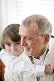 Grandfather getting hug from grandson Stock Image