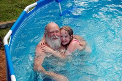 Grandfather and girl in pool. Aerial view of bearded mature man/grandfather hugging girl in swimming pool Stock Photography