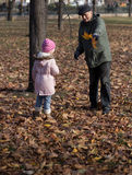 Grandfather gives her niece autumn leaves. Stock Photos
