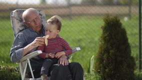 Grandfather giving banana to his grandson outdoor. stock video footage