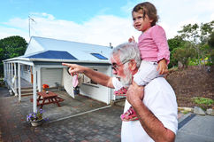 Grandfather Giving Grandchild Ride on Shoulders Stock Photo