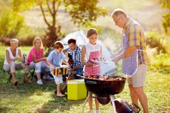 Grandfather giving granddaughter grilling meat royalty free stock image