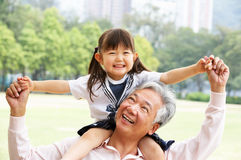 Grandfather Giving Granddaughter Ride On Shoulders Stock Image