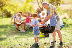 Grandfather giving grandson barbecue food Royalty Free Stock Photo