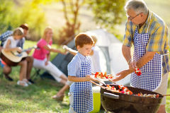 Grandfather giving grandson grilled meat Stock Photos