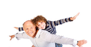 Grandfather giving grandson piggy-back Royalty Free Stock Photo