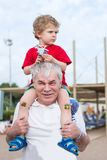Grandfather Giving Grandson Ride On Shoulders Outdoors Royalty Free Stock Photo