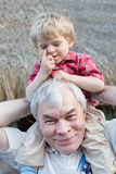 Grandfather Giving Grandson Ride On Shoulders Outdoors Royalty Free Stock Photos