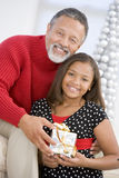 Grandfather Giving His Granddaughter A Present. Grandfather Giving His Granddaughter A Christmas Present Royalty Free Stock Photography