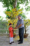 Grandfather giving lucky money to grandson on the first day of Vietnamese lunar new year Tet stock image