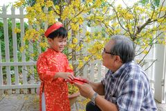 Grandfather giving lucky money to grandson on the first day of Vietnamese lunar new year Tet stock photo