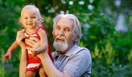 Grandfather and grand daughter. The grandfather sits on a lawn and holds the cheerful grand daughter on hands. They are shined by the coming sun Royalty Free Stock Photos