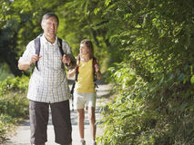 Grandfather and grandaughter hiking in wood Royalty Free Stock Photo
