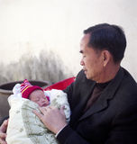 Grandfather and grandchild. A chinese grandfather is holding his new born grandchild in his arm. Photo by film stock image