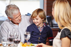 Grandfather and grandchild. Family with smiling grandfather and his grandchild eating out in a restaurant royalty free stock photo