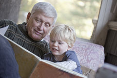 Grandfather and grandchild reading. Grandfather reading a book to his grandchild stock photos