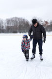Grandfather with grandchild at the skating rink Stock Photos