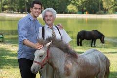 Grandfather and grandchild stroking pony. Image of grandfather and grandchild stroking pony Royalty Free Stock Photos