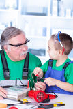 Grandfather and grandchild using multimeter Royalty Free Stock Photo