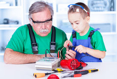 Grandfather and grandchild using multimeter. Grandfather with grandchild measuring continuity with analogic multimeter royalty free stock photography