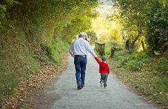 Grandfather and grandchild walking in nature path. Back view of grandfather and grandchild walking in a nature path stock images
