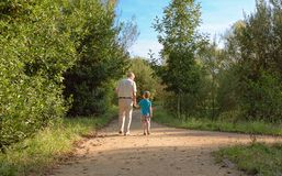 Grandfather and grandchild walking outdoors Stock Photos