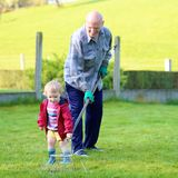 Grandfather and grandchild working in the garden Stock Photo