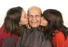 Grandfather and grandchildren. Two young adolescent girls kissing their grandfather Stock Photography