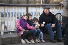 Grandfather with grandchildren eating ice cream while sitting on the parapet on Southbank Royalty Free Stock Photo