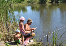 Grandfather and grandchildren fishing. On the lake in the summer Stock Photo