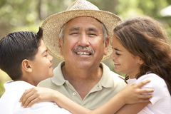 Grandfather With Grandchildren In Garden. Hispanic Grandfather With Grandchildren In Garden Smiling royalty free stock images