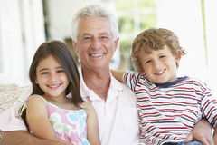 Grandfather With Grandchildren At Home Royalty Free Stock Photos