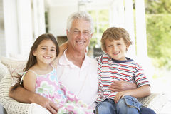 Grandfather With Grandchildren At Home Stock Photos