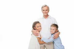 Grandfather and grandchildren hugging together. Smiling grandfather and grandchildren hugging together, isolated on white stock photos